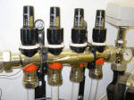 Adjustable flow regulators on an underfloor heating manifold
